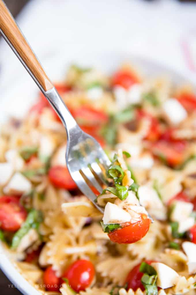Caprese Pasta Salad with pasta, tomato and mozzarella cheese on a fork
