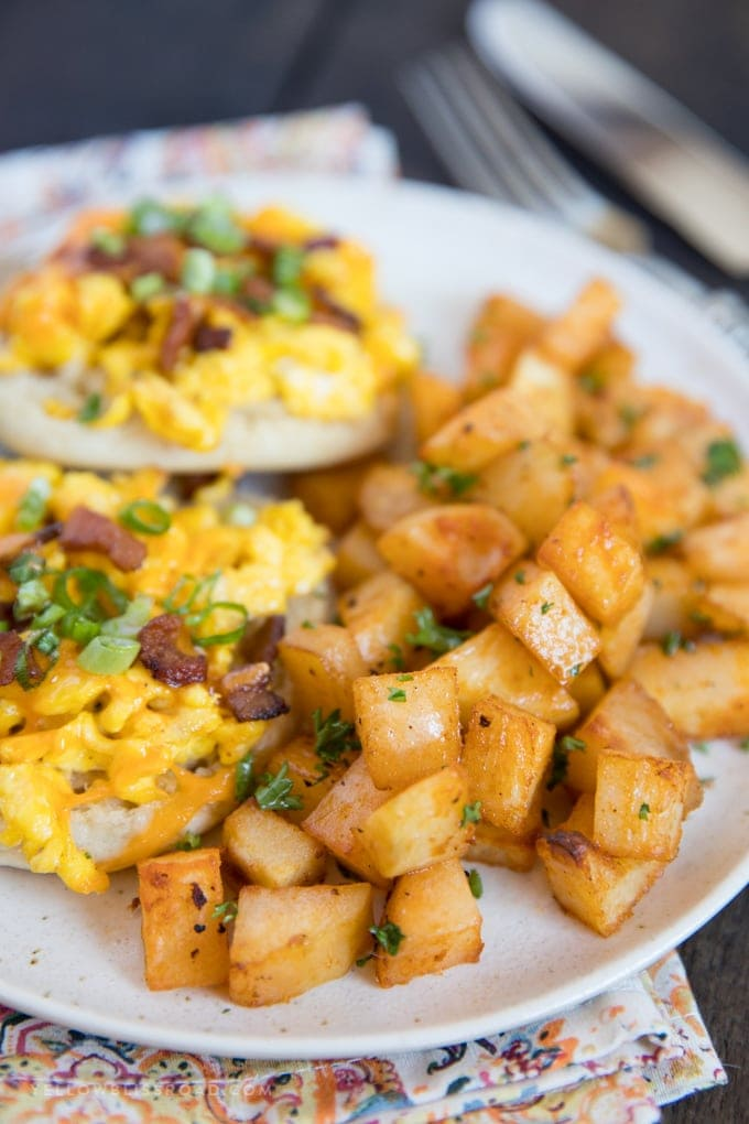 Easy Breakfast Potatoes served on a white place alongside english muffin breakfast pizzas