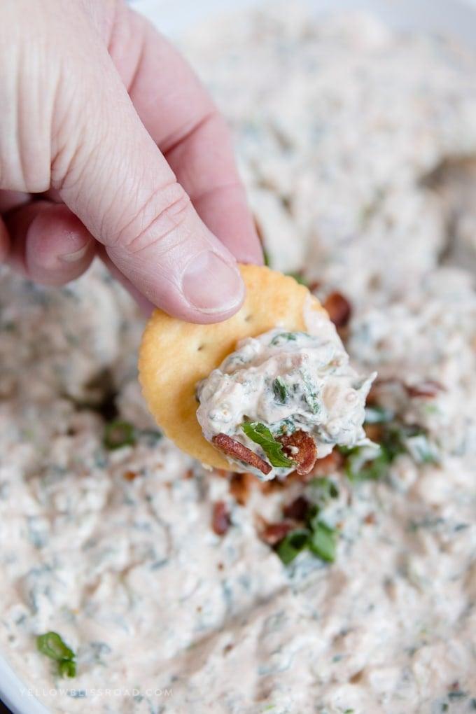 Bacon Garlic Spinach Dip on a cracker