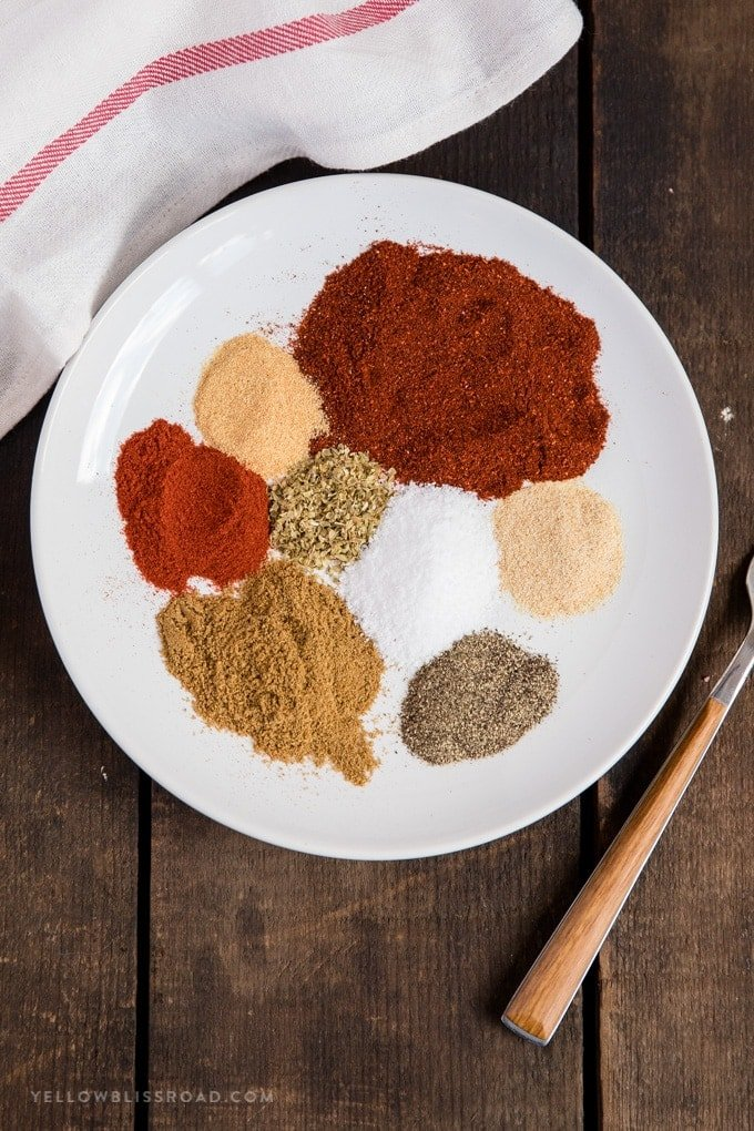 Homemade taco seasoning divided into separate ingredients on a plate
