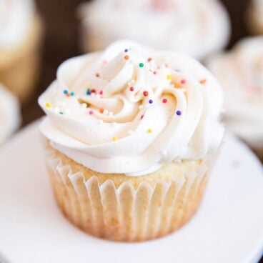 A close up of a vanilla cupcake on a plate, with vanilla frosting
