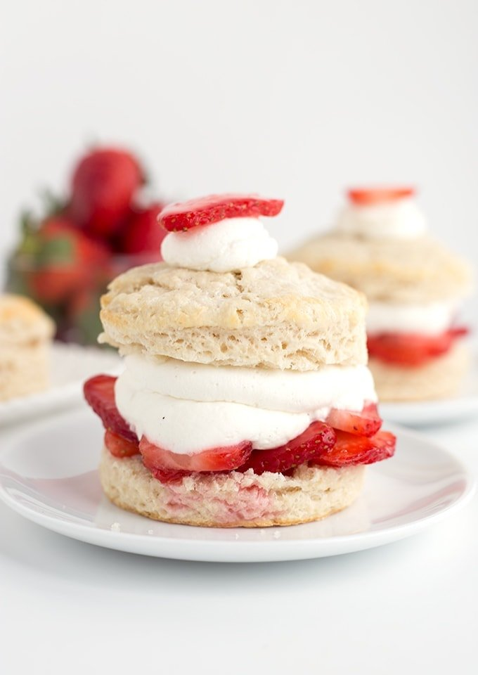 Strawberry shortcakes on dessert plates, topped with sliced strawberries
