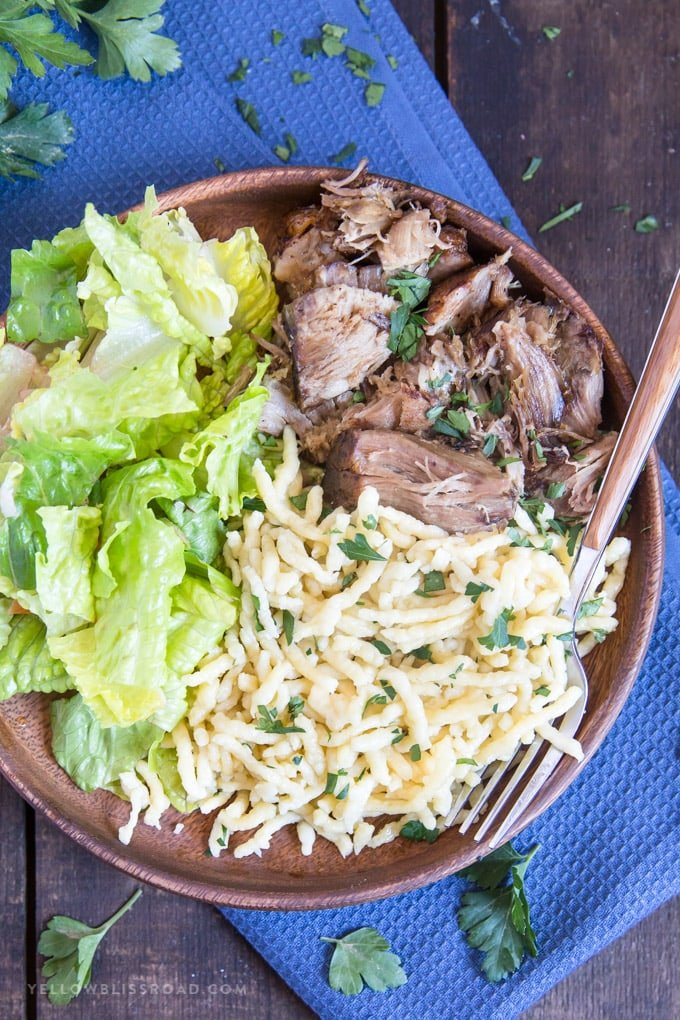 German Spaetzle on a wooden plate with pork roast and salad