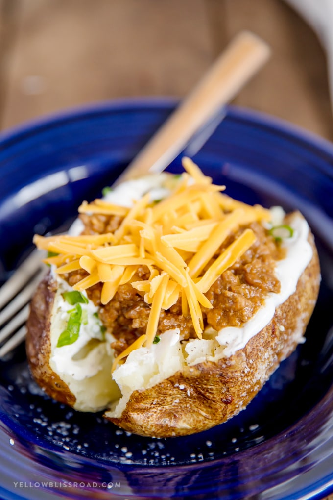 Taco Stuffed Baked Potato with cheese and taco meat in a blue pasta bowl