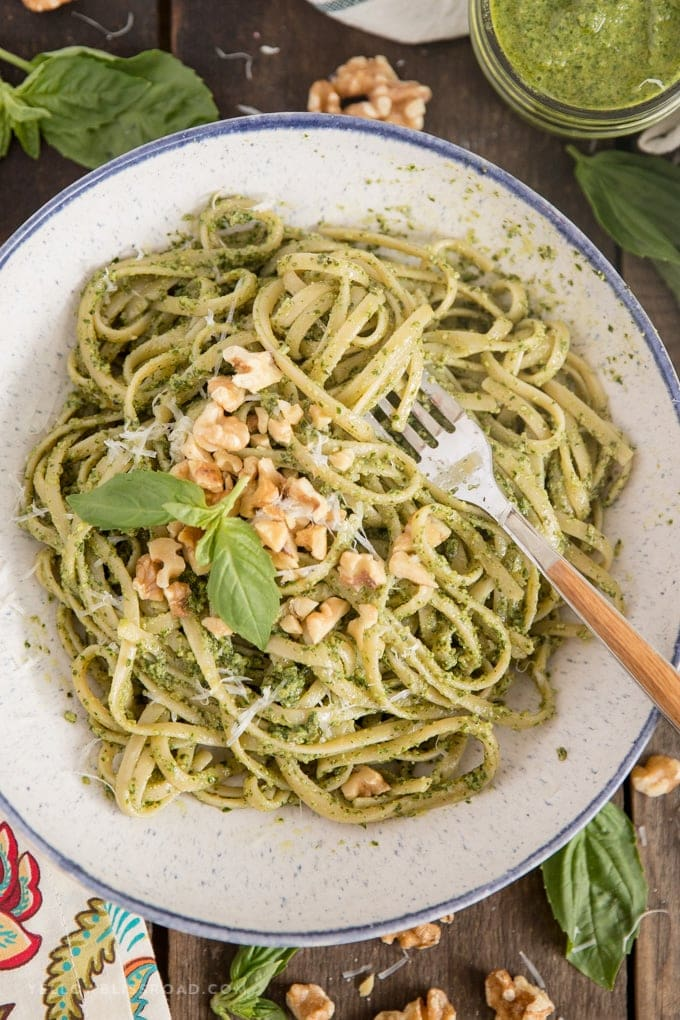 Homemade Walnut Basil Pesto recipe over pasta in a large bowl with a wooden fork.