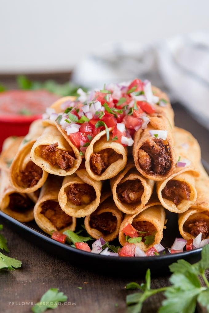Fried chicken taquitos with pico de gallo garnish