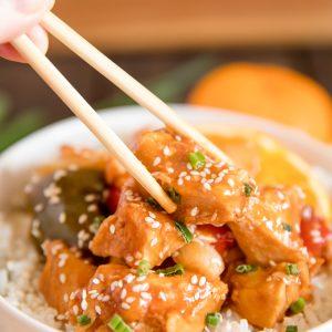 orange chicken, bell peppers, rice, sesame seeds, white bowl, chopsticks