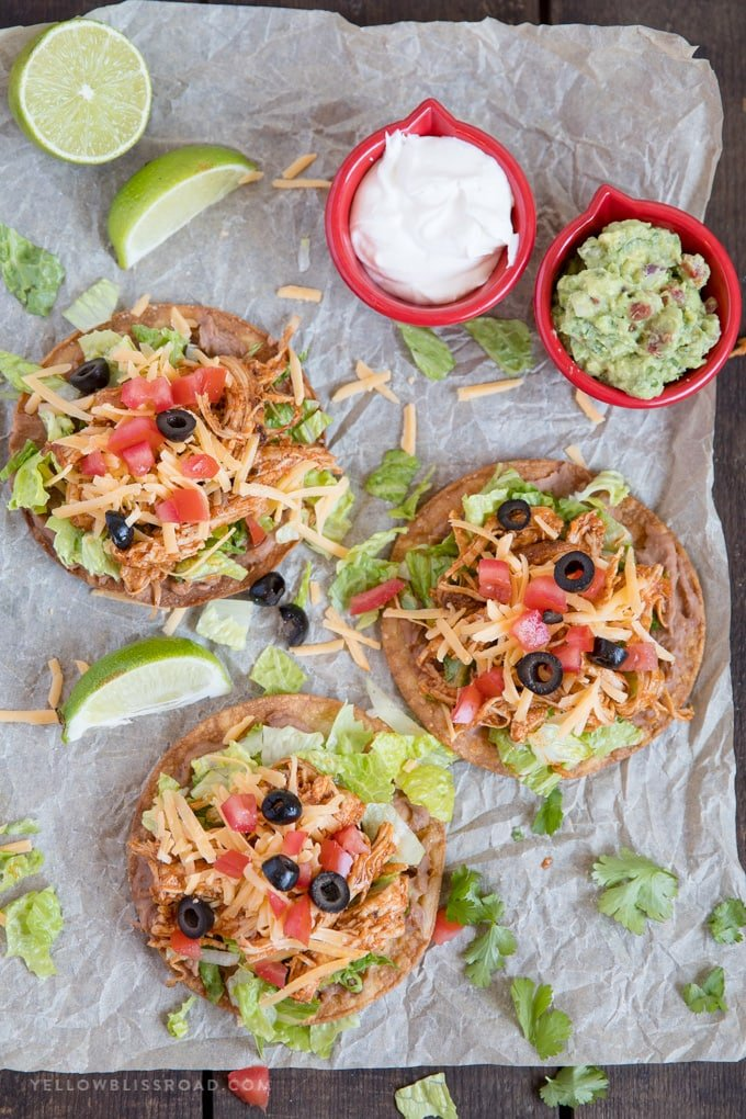 Overhead photo of 3 chicken tostadas with toppings.