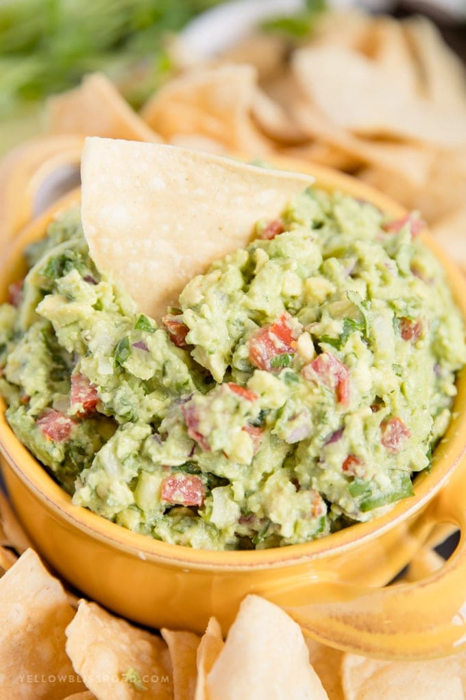 a chip in a bowl of the best guacamole