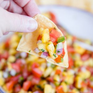 Chip dipping into bowl of Fresh Pineapple Salsa