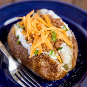 A blue plate with a taco stuffed potato