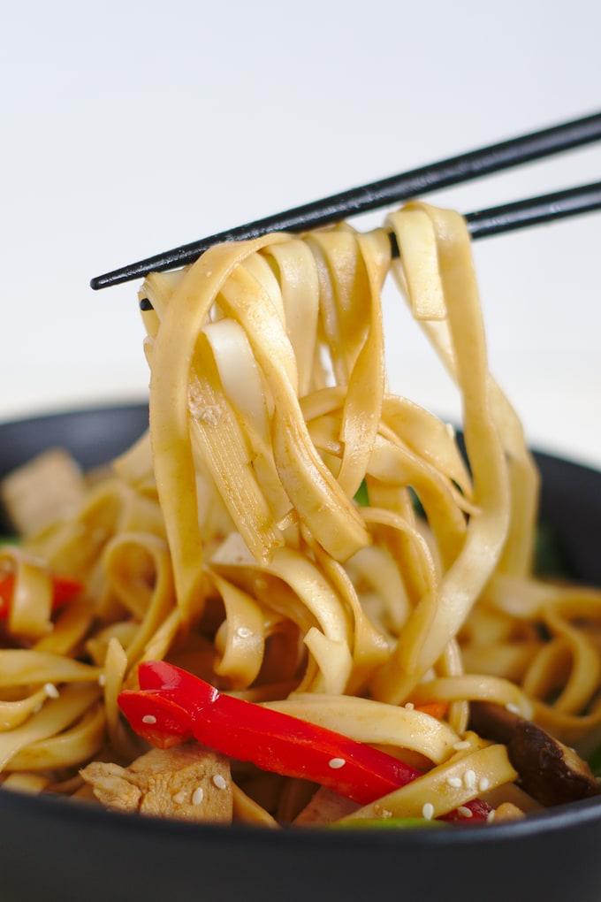 Chopsticks holding up chicken lo mein noodles