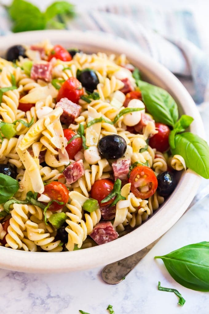 bowl of antipasta pasta salad with basil leaves for garnish