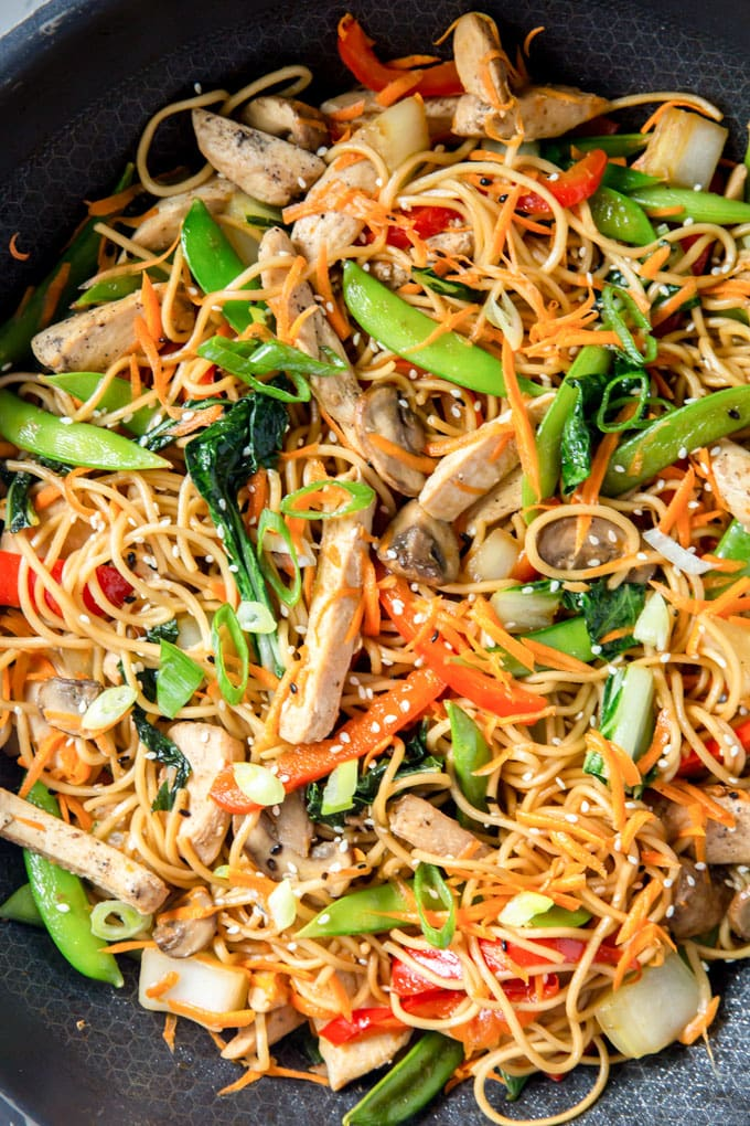 a close up overhead image of chicken lo mein with vegetables.