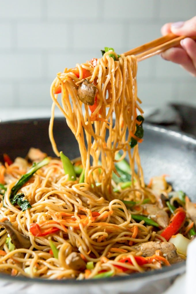A hand holding chopsticks lifting up a serving of chicken lo mein from a large skillet