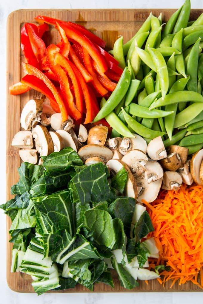 Chopped up bell pepper, mushrooms, bok choy, carrots and snow peas on a wooden cutting board