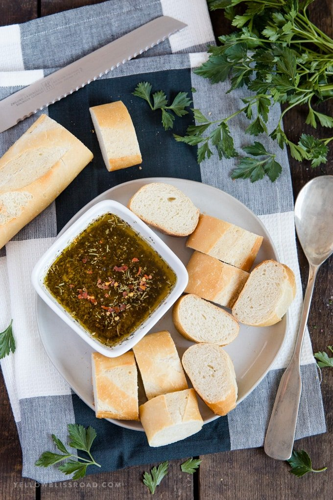 a plate of slice french bread with a dipping bowl of garlic herb olive oil bread dip