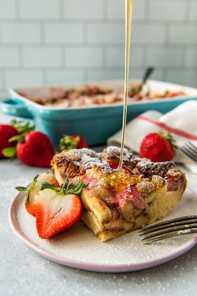 A piece of baked french toast with strawberries and a strem of syprup being poured on top.