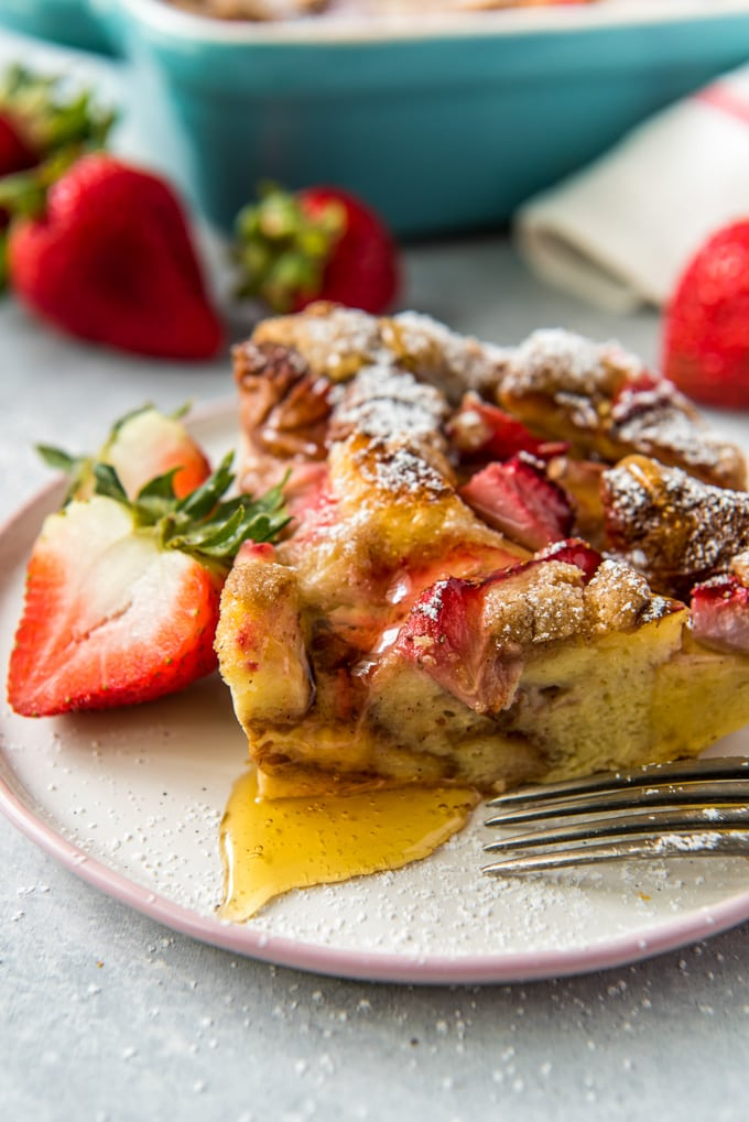 A piece of strawberry baked french toast with syrup on a white plate and topped with syrup and powdered sugar.