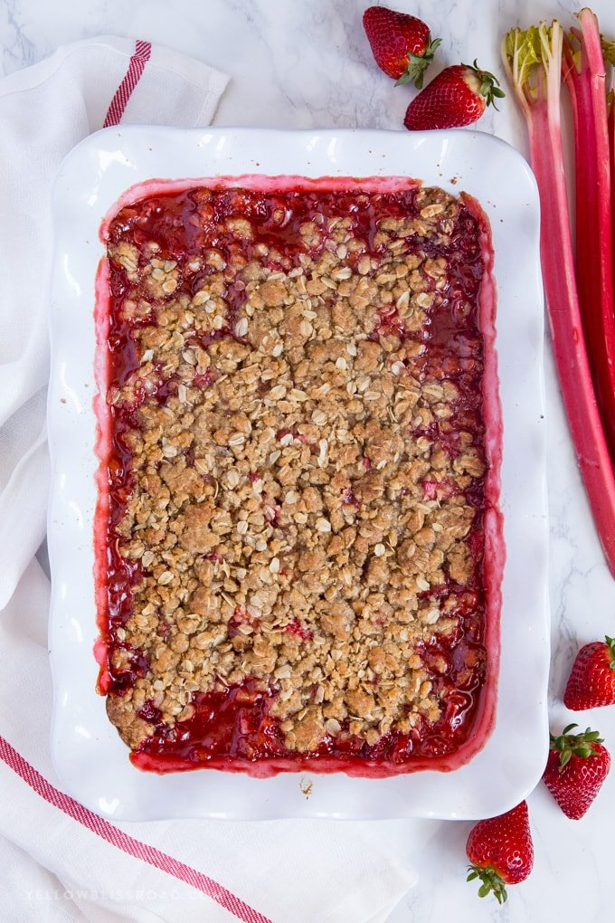 Strawberry Rhubarb Crisp in a white ruffled baking dish