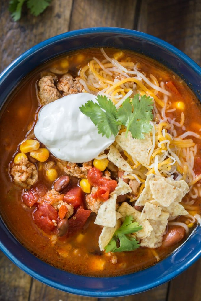 a bowl of taco soup with sour cream, tortilla chips and cilantro on top