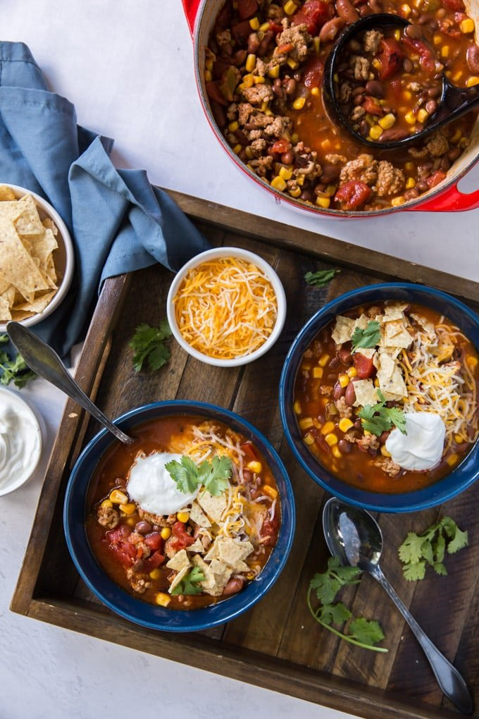 A bowl filled taco soup and side dish of shredded cheese.
