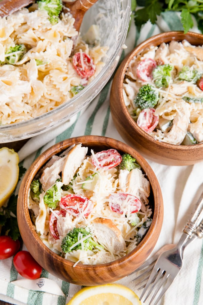 pasta salad in wooden bowls with tomatoes and broccoli.