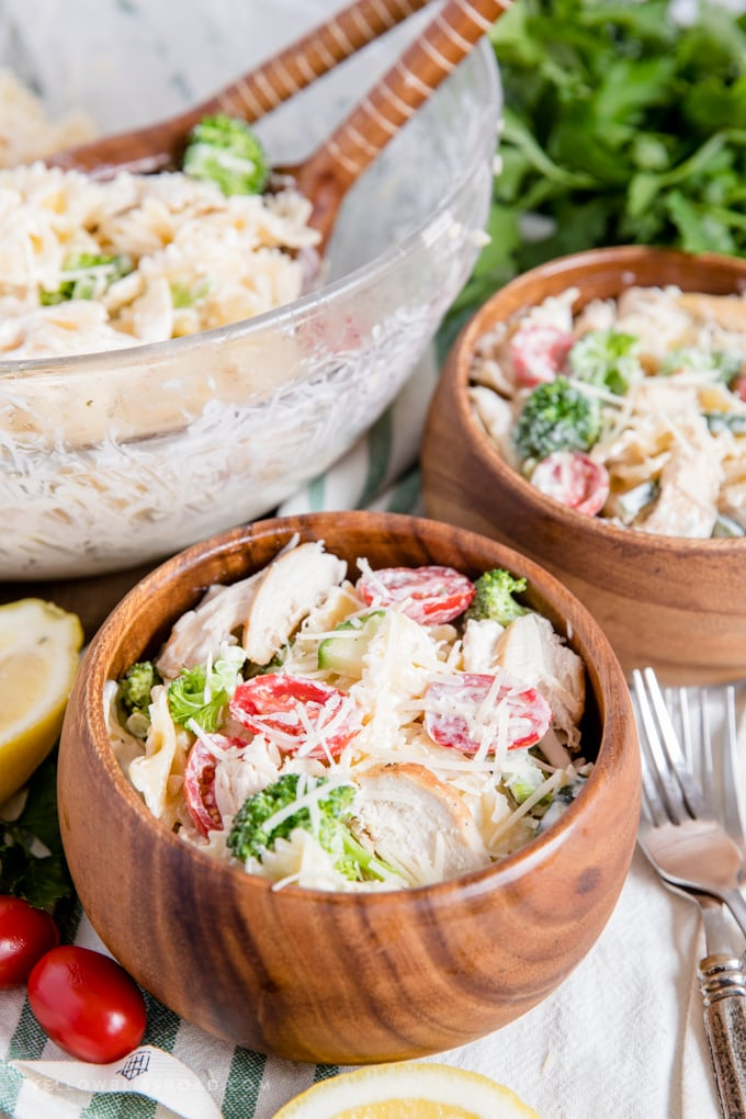 45 degree angle shot of chicken pasta salad in wood bowls and in a large glass bowl. wooden spoons parsley