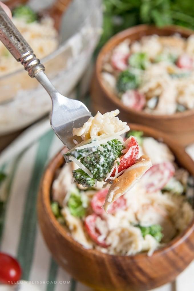 chicken pasta salad in wooden bowls, chicken, brocoli, toamto on a fork