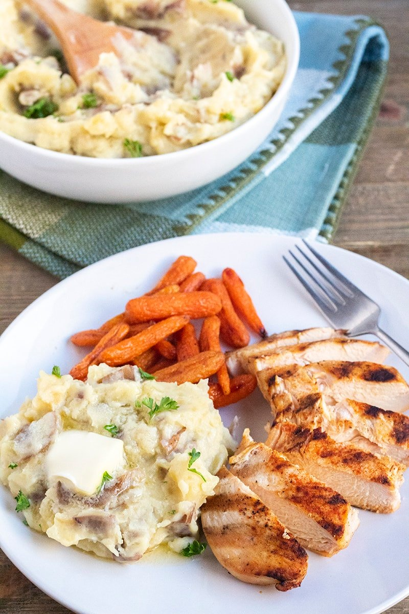 garlic mashed potatoes on a dinner plate with honey roasted carrots and grilled chicken