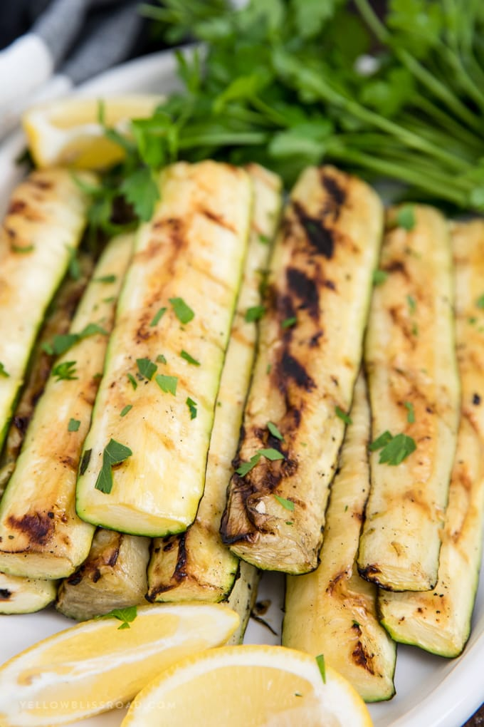 grilled zucchini strips on a plate with lemon.