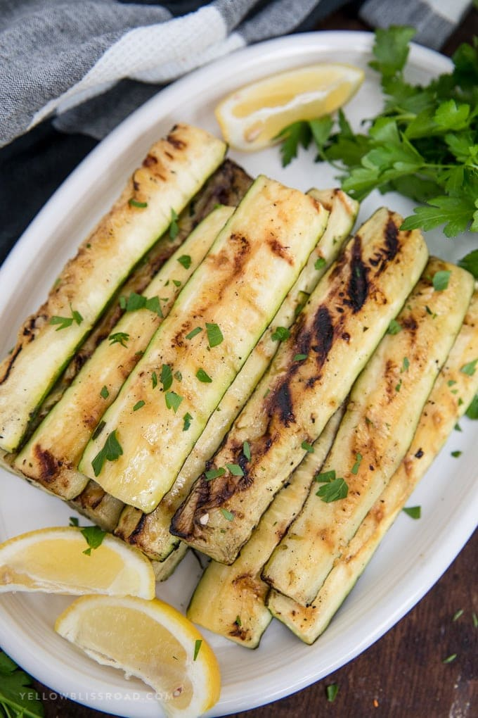Grilled zucchini cut into strips on a plate with lemon and parsley.