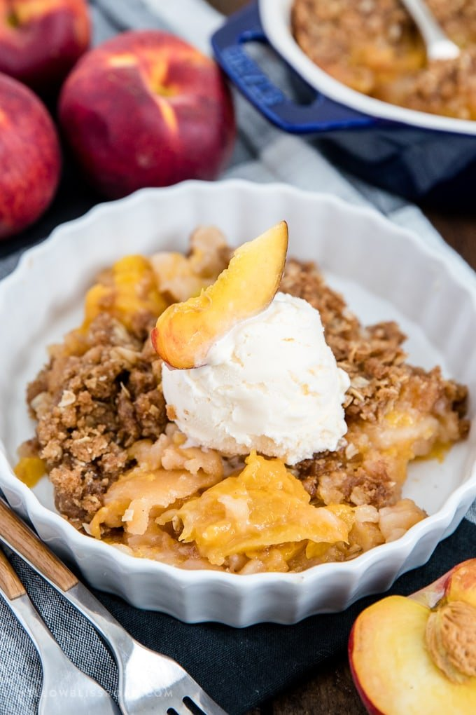 Fresh peach crisp in a dish with a scoop of vanilla ice cream.