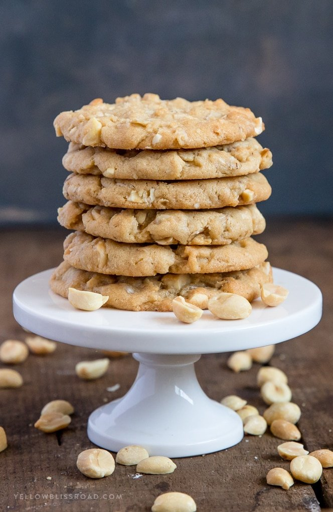 A stack of oatmeal peanut butter cookies on a small plate with peanuts scattered around.