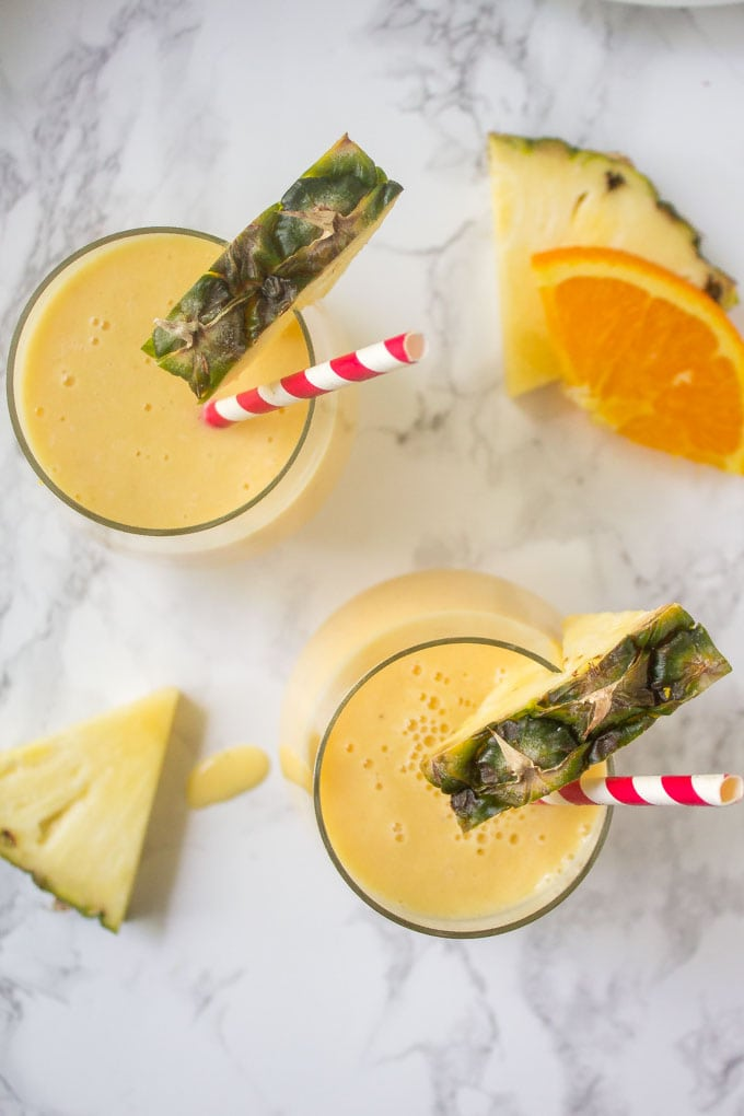 overhead shot of pineapple smoothies in glasses with pineapple and orange slices in the background