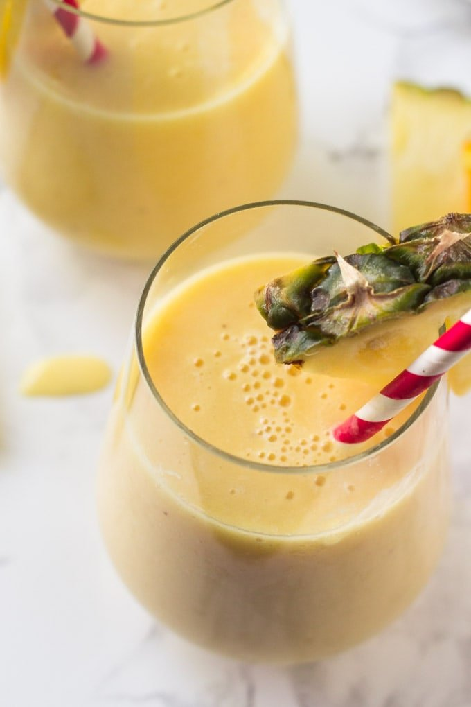 pineapple smoothie in a glass with a straw and pineapple wedge