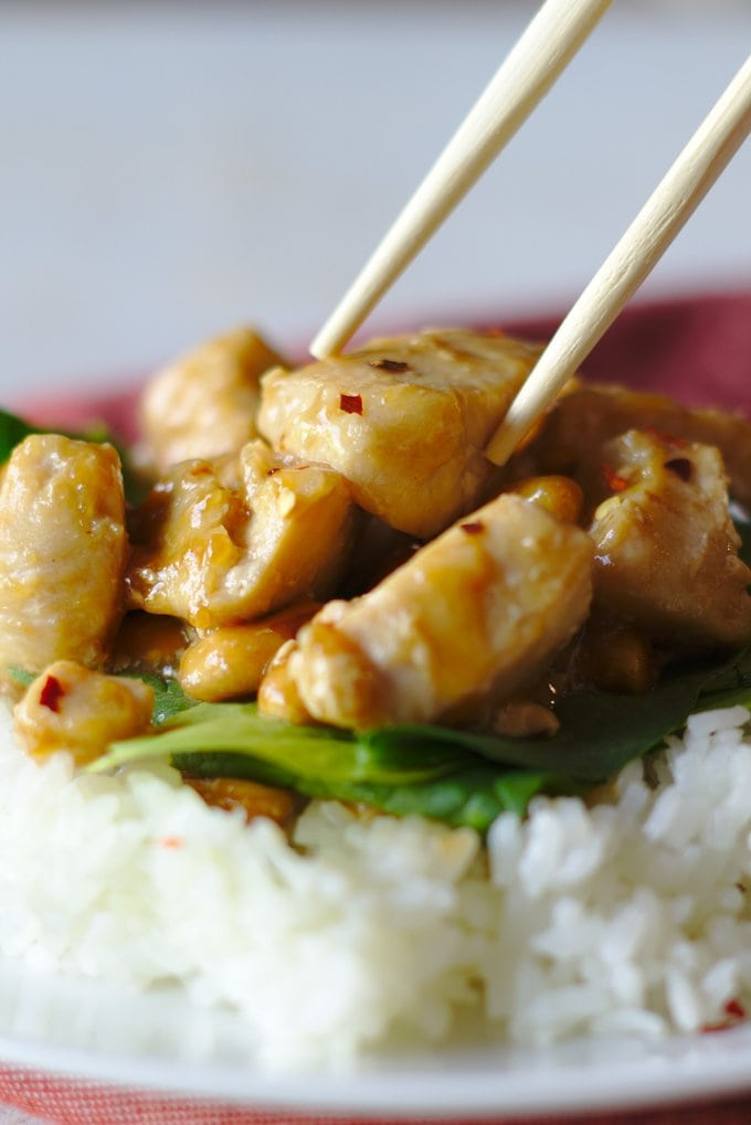 Chopsticks grabbing a piece of Kung Pao Chicken