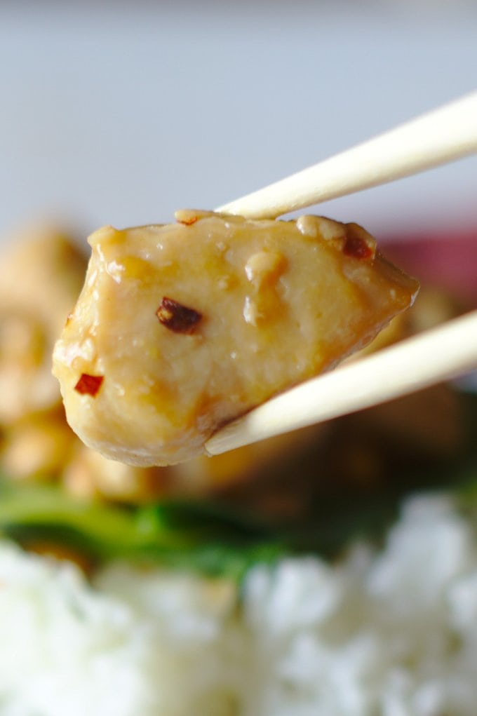 close up of chopsticks holding up a piece of Kung Pao Chicken