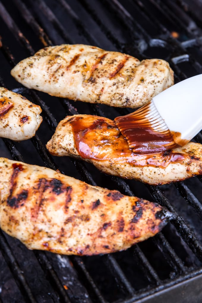 Black grill grates, 4 chicken breasts with grill marks, a white pastry brush with bbq sauce