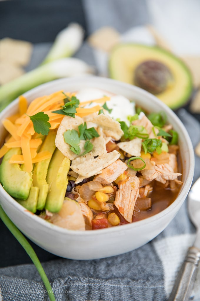 Chicken Tortilla Soup in a bowl with sliced avocado, cheese and sour cream.