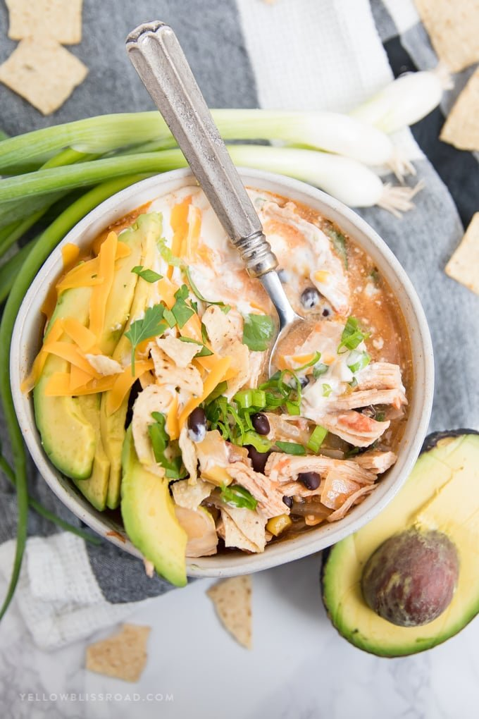 Chicken Tortilla Soup in a bowl stirred with sour cream and topped with avocado.
