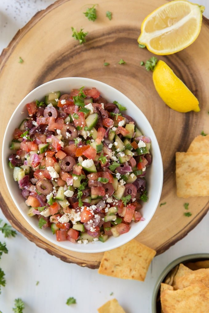 a large, round wood board with a small bowl of greek salsa, surrounded by a few pita chips and lemon slices.
