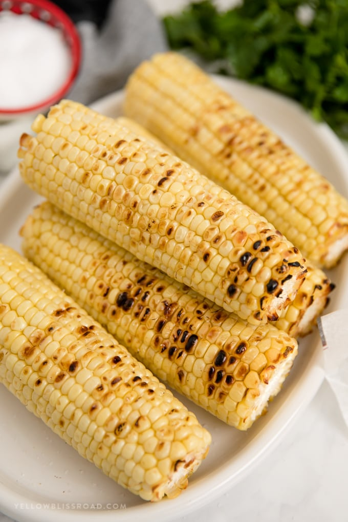 a platter of grilled corn on the cob