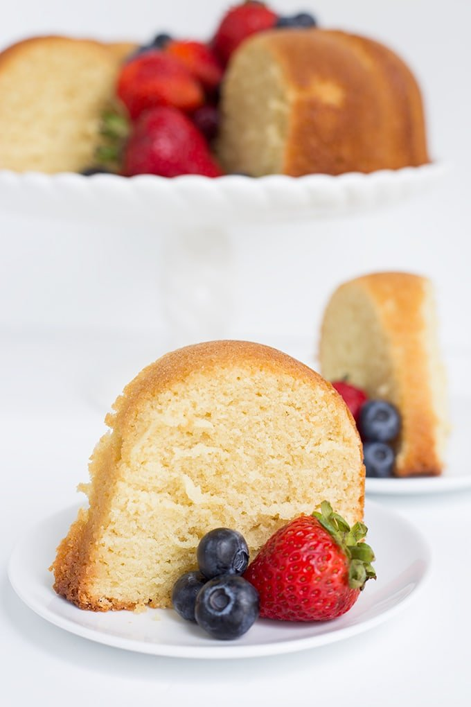 slice of pound cake on a dessert plate with fresh berries