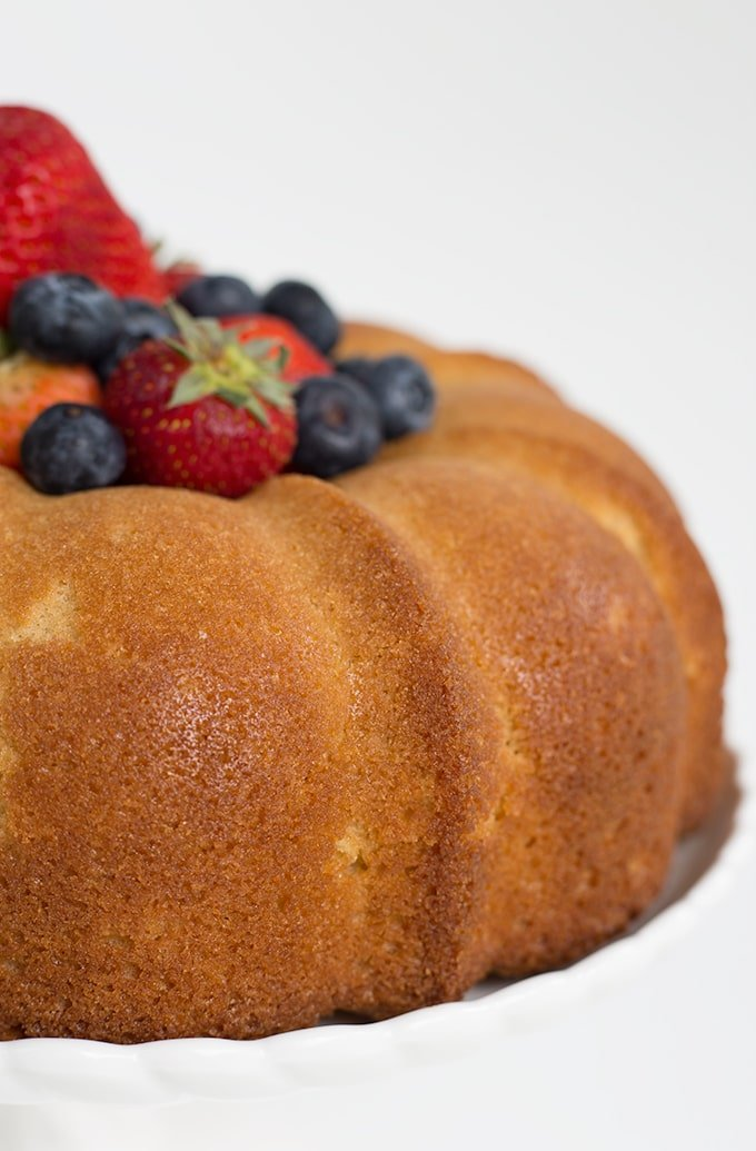 pound cake recipe made in a bundt pan and topped with fresh berries