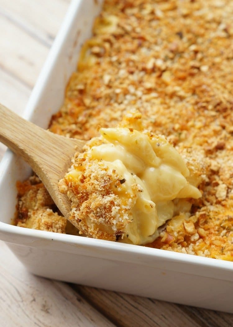 wooden spoon serving baked macaroni and cheese from casserole dish