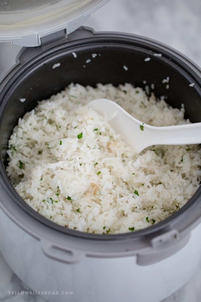 Coconut rice in a rice cooker with a white spoon