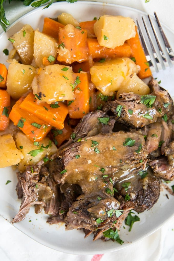 crock pot roast served on a plate with carrots, potatoes and gravy.