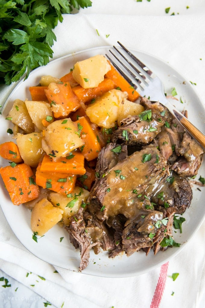 Crock pot roast | Slow cooker pot roast served on a white plate with carrots, potatoes and gravy.