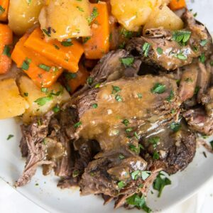 A plate of Pot Roast with gravy and veggies